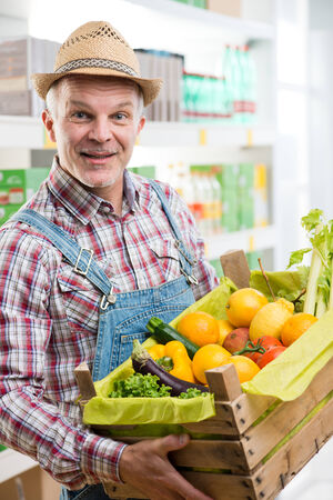 crate: Farmer holding a wooden crate with fresh vegetables and fruits at supermarket.