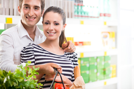 Happy young couple smiling and holding a full shopping basket at supermarket. photo