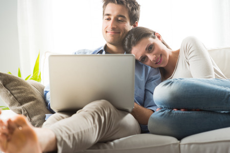 couple couch: Young couple relaxing on sofa with laptop in the living room. Stock Photo
