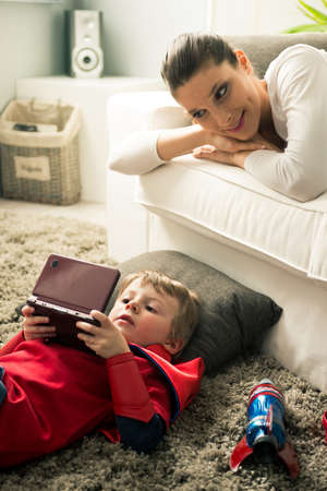 Little superhero boy playing videogames and mother lying down on sofa in the living room. photo