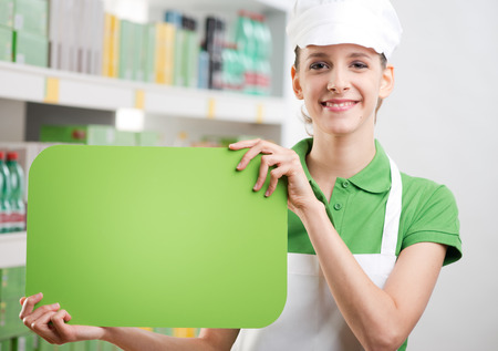 sales clerk: Female sales clerk holding a green sign and smiling with supermarket shelf on background. Stock Photo