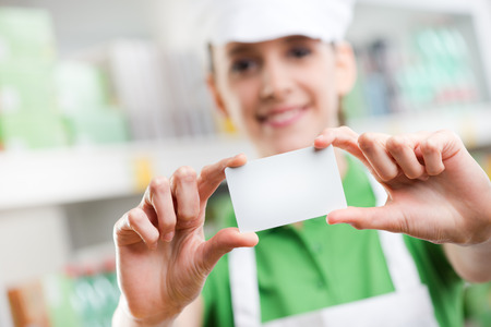 sales clerk: Female sales clerk holding a white card and smiling with supermarket shelf on background.