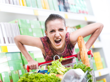 woman shopping cart: Angry woman pushing a full shopping cart at store with shelves on background.