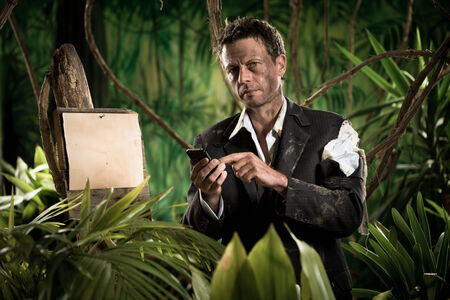 business survival: Lost businessman in torn clothing using mobile phone in the jungle.