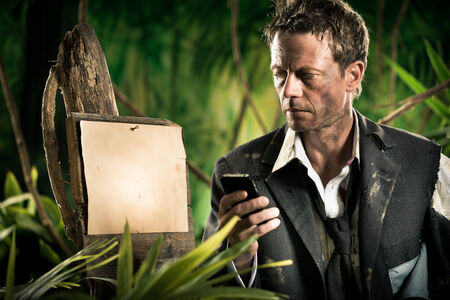 office wear: Businessman lost in jungle with mobile phone and empty sign. Stock Photo