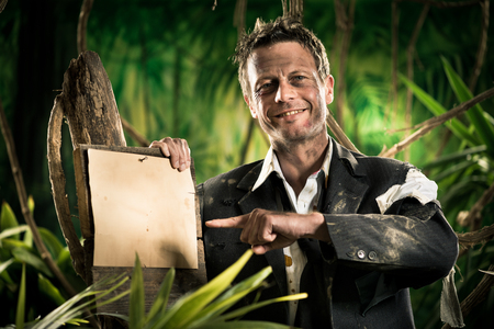 business survival: Confident smiling businessman in the jungle pointing at sign. Stock Photo
