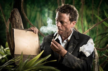 office wear: Businessman lost in jungle lighting a cigarette next to a no smoking sign. Stock Photo