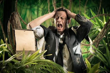 office wear: Desperate businessman lost in jungle with head in hands and empty sign. Stock Photo