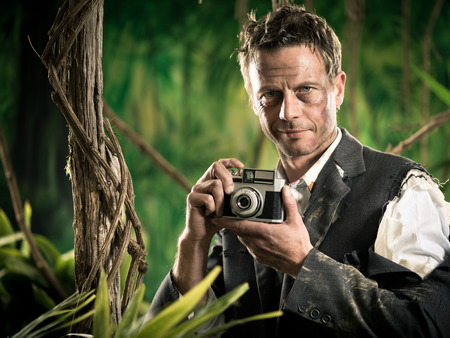 office wear: Attractive man in torn clothing walking in jungle with vintage camera.