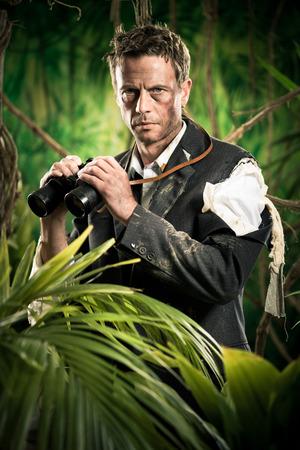 Confident businessman holding binoculars and exploring jungle. photo