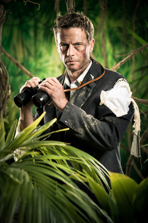 business survival: Confident businessman holding binoculars and exploring jungle.