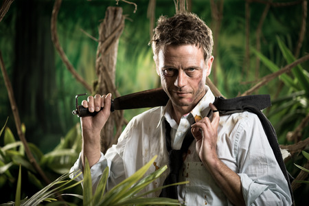 business survival: Attractive confident businessman with machete walking in the jungle.