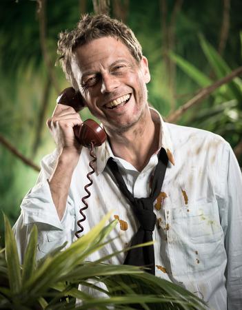 oficina desordenada: Sonriente hombre de negocios atractiva que habla en el tel�fono en la selva con la ropa rasgada. Foto de archivo