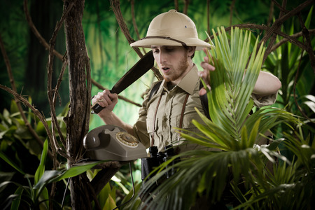 machete: Young explorer with machete finding a vintage telephone in the jungle.