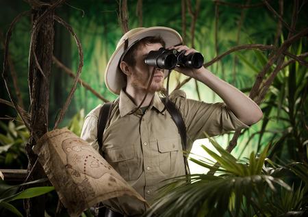 Expert explorateur dans la jungle regardant loin avec des jumelles.