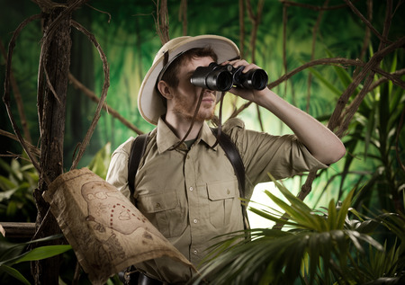 Expert explorer in the jungle looking away through binoculars.