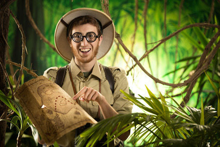 Young smiling explorer in the jungle with thick glasses holding a map. photo