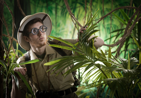 Young explorer guy walking in the rainforest jungle with exploration equipment and thick glasses. Reklamní fotografie
