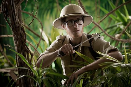 machete: Watchful young adventurer holding a machete walking through the jungle.