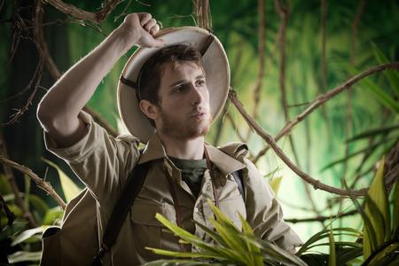 médula: Aventurero joven cansado de explorar el bosque con la mano en el sombrero de médula.