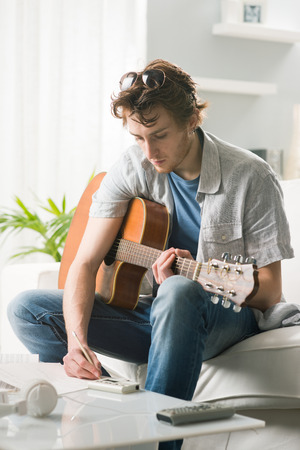 composing: Young man playing guitar and composing a song sitting on sofa. Stock Photo