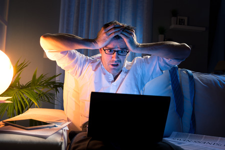 displeased businessman: Shocked businessman with head in hands staring at laptop screen late at night. Stock Photo