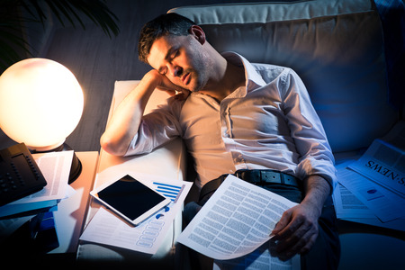 tired businessman: Tired businessman sleeping on sofa at home surrounded by paperwork.
