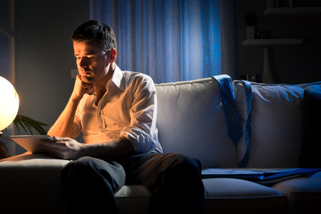 Businessman working overtime late at night in the living room, with tablet and paperwork.