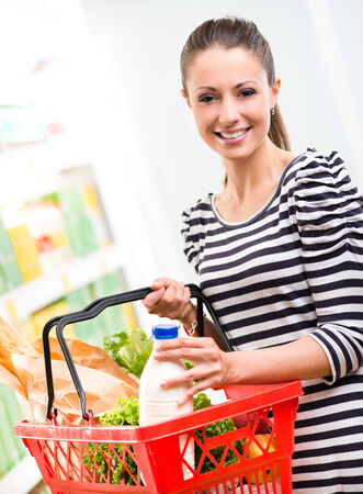 Smiling woman at supermarket with full shopping basket and shelves on background. photo