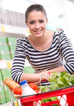 Attractive smiling woman shopping at store leaning to shopping cart. photo