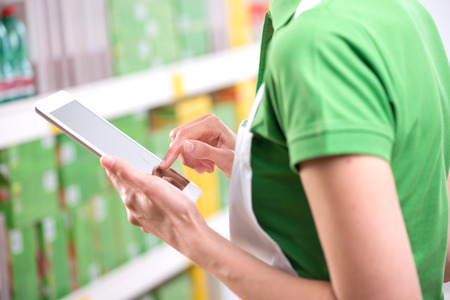Sales clerk wearing apron using a digital tablet with store shelves on background. photo