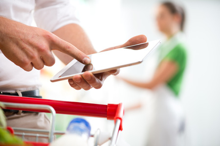 Customer using a digital tablet at supermarket with sales clerk on background. photo