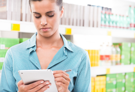 Young woman with digital tablet and stylus at supermarket with store shelves on background. photo