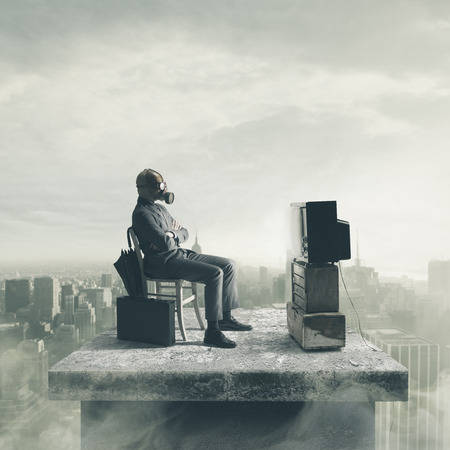 Businessman wearing a gas mask watching TV Stockfoto