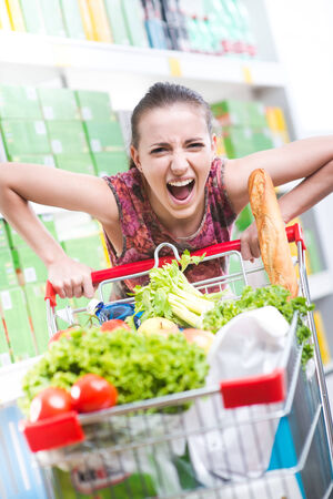 overburdened: Angry woman pushing a full shopping cart at store with shelves on background.