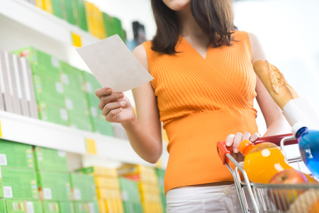 Young woman holding a shopping list an searching products on shelves. photo