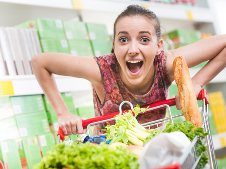 Woman mouth open pushing a full heavy shopping cart at supermarket.