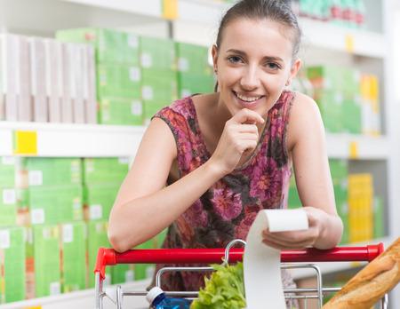 mujer pensativa: Mujer sonriente que controla un recibo largo e inclinado a un carrito de la compra lleno en el supermercado. Foto de archivo