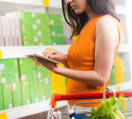 Young woman using a digital tablet at store with supermarket shelves on background. photo