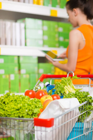 Woman using tablet at store with grocery on foreground. photo