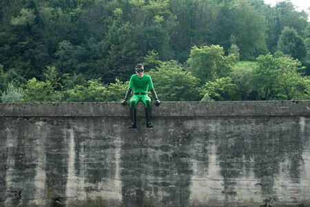 fictional character: Green superhero sitting on a high concrete wall with lush forest