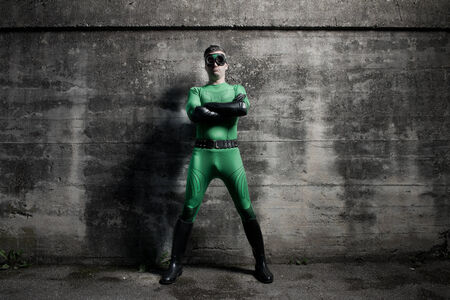 Confident superhero standing with arms crossed against a concrete wall.