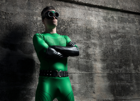 invincible: Confident superhero standing with arms crossed against a concrete wall.