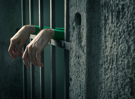 ancient prison: Man in jail hands close-up, depression and despair concept.