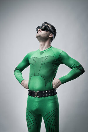 inefficient: Funny lazy superhero looking up with arms akimbo.