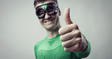 good attitude: Cheerful green superhero thumbs up looking at camera.
