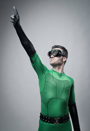 Brave green superhero pointing up and smiling confidently. photo