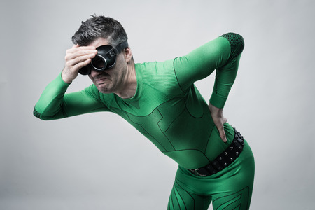 Sad superhero bent over with back pain touching his head and back. Stock Photo