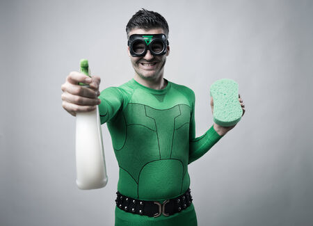 funny guys: Confident green superhero with eco-friendly spray detergent and sponge. Stock Photo
