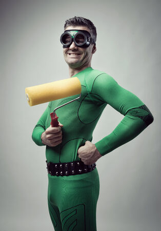 redecoration: Funny cheerful superhero holding a painting roller and smiling at camera.